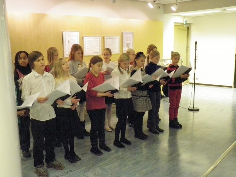 Eduskunnan kirjaston perinteisillä jouluglögeillä kuultiin musiikkiluokan esitys ja sitten tarinoita eri Suomenmaan murteilla.