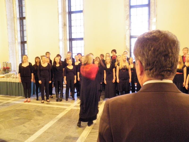 Puhemies Sauli Niinistö kuuntelemassa Sibelius lukion kuoron joulutervehdystä.