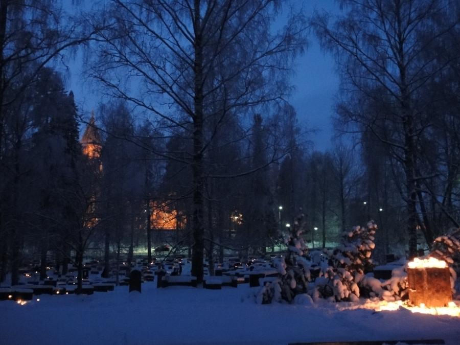 Ja hautausmaalla tottakai käynti läheisten haudoilla kuului tänäkin vuonna jouluaaton ohjelmaan. Taustalla Lopen uusi kirkko.