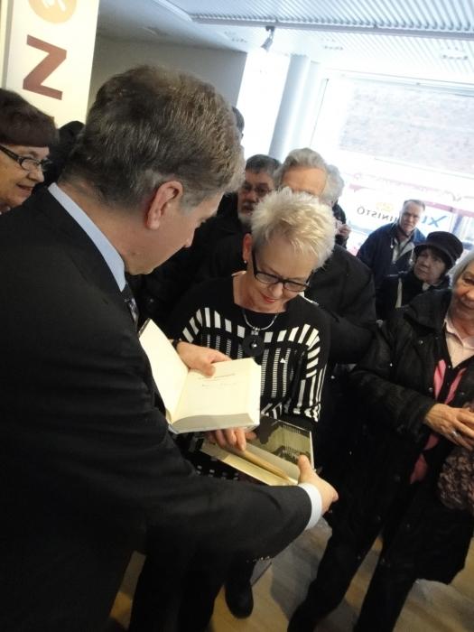 Ja kirjakauppiaalle nimikirjoituksia. Marjatta Järvinen saa allekirjoitukset keräilyharvinaisuus kirjoihin Sauli Niinistöltä.