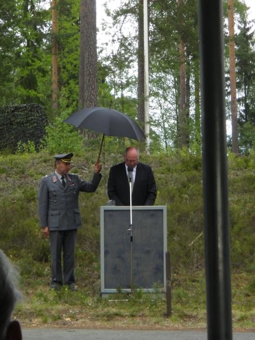 Eduskunnan tervehdyksen juhlaan toi puhemies Eero Heinäluoma, joka pääsi sateen yllättäessä presidentin sateenvarjon suojiin.