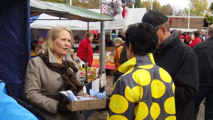 Mira Eriksson jakamassa esitteitä ja juttelemassa kuntalaisten kanssa.