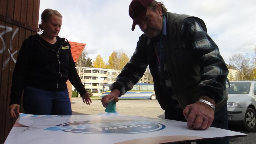 Mira Eriksson Erkki Holttisella kanssa tarkistamassa, että mainos on suorassa ja siististi ja tärkeintä, että kumpikin puoli oikea reuna ylöspäin :)