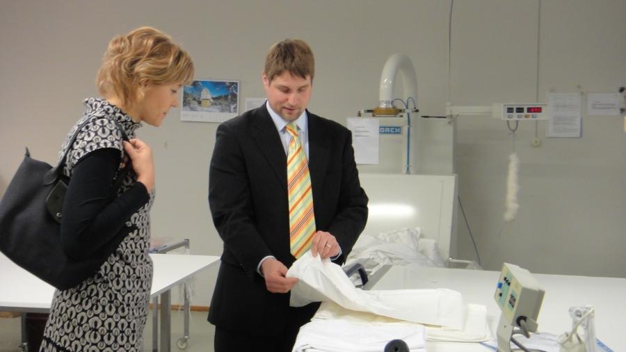 Tuomas Laine esittelee Henna Virkkuselle suomalaisen untuvapeitteen valmistusta Riihimäen tehtaalla.