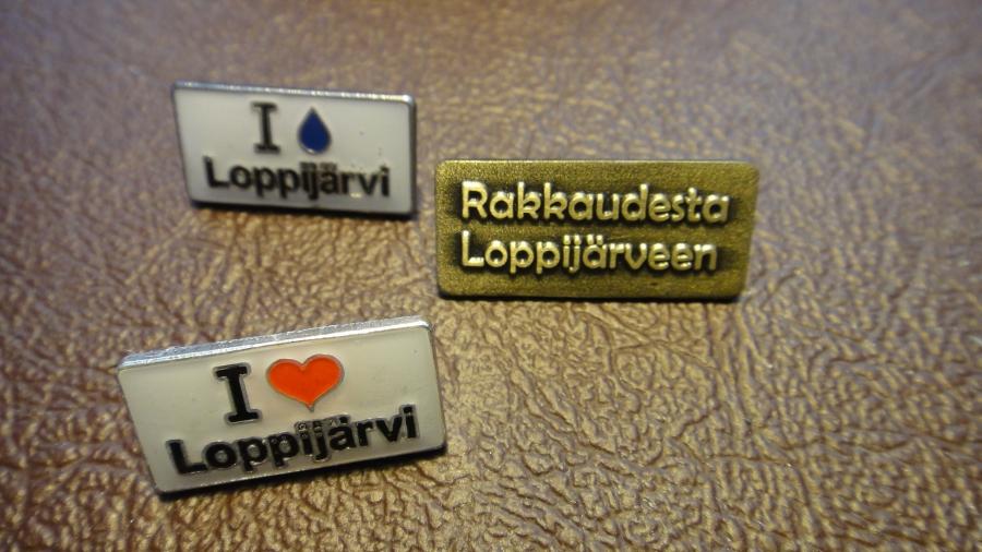 Tässä kolme vuosipinssiä Loppijärvemme hyvöksi. Oikealla tämän vuoden keräilypinssi ja vasemmalla ylhäällä vuoden 2012 pinssi ja alhaalla vasemmalla ensimmäinen I love Loppijärvi -pinssi vuodelta 2011.