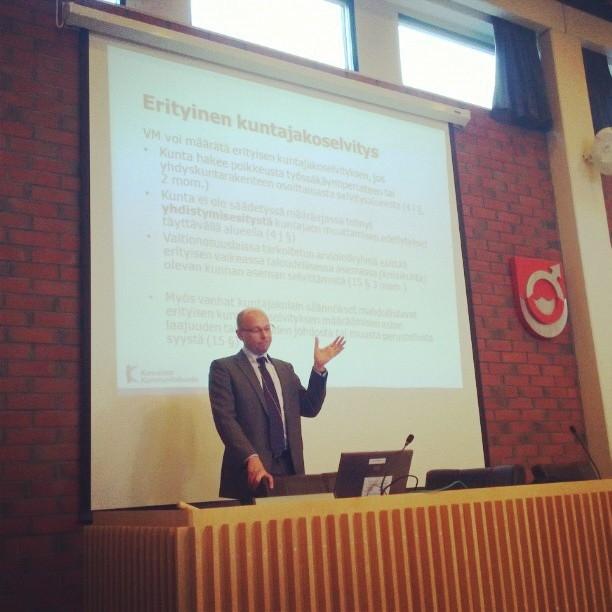 Kuntaliiton johtava lakimies Juha Myllymäki esittelee kuntarakennelakia ja sen vaatimuksia ja tavoitteita Riihimäen, Hausjärven ja Lopen valtuutetuille Lopen valtuustosalissa.