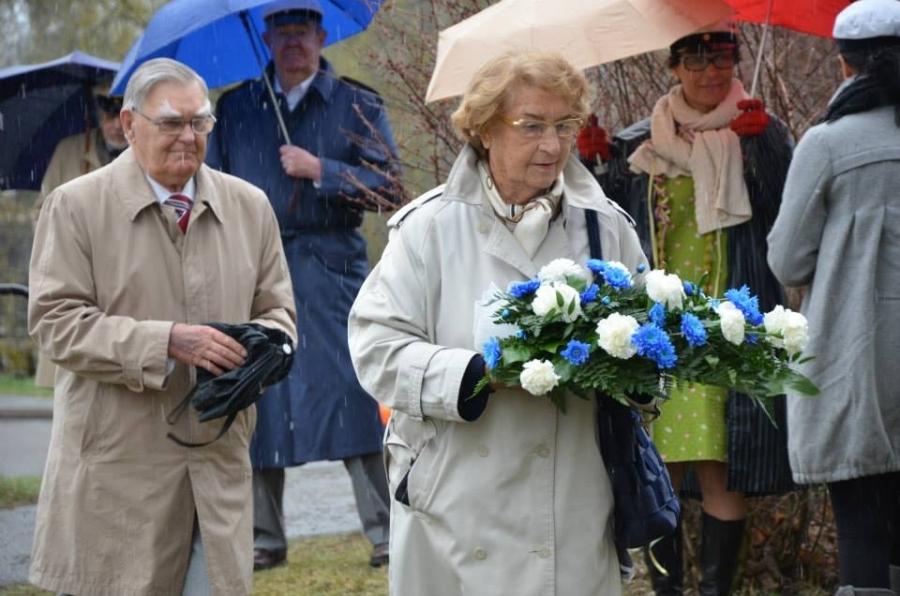 Suvun vanhin laski tavan mukaan sinivalkoiset kukat senaattori Yrjö Sakari Yrjö-Koskisen patsaalle.