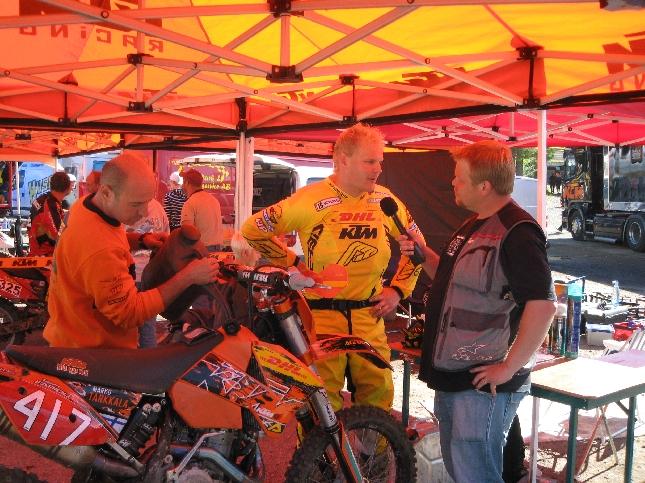 Marko Tarkkala haastateltavana Heinolan EM-enduron huollossa. Luca uurastaa pyörän kimpussa.