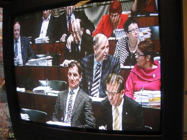 Uusi iloinen SDP! - Työhuoneiden tv:t välittävät kuvaa täysistunnosta.