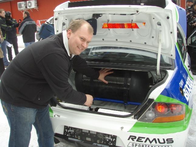 Maakaasuauton Suomeen yhdessä Mitsubishin kanssa tuonut rallikuljettaja Jani Paasonen. Takaluukussa näkyy toinen säiliöistä. Siviililiikenteen autoihin muuten on mahdollista saada myös kotitankkaus jos talossa maakaasujärjestelmät. Tällöin polttoaine vielä normijakeluasemiakin halvempaa. Normaali hinnan ero bensaan on reilu puolet - edullisempaa siis.