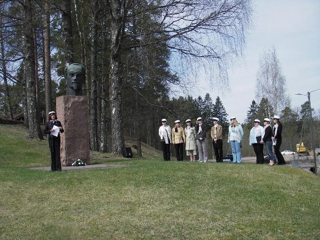 Hannele Yrjö-Koskinen puhuu sukunsa suurmiehen Yrjö Sakari Yrjö-Koskisen patsaalla. Puhetta kuuntelevat Timotein laulajat.