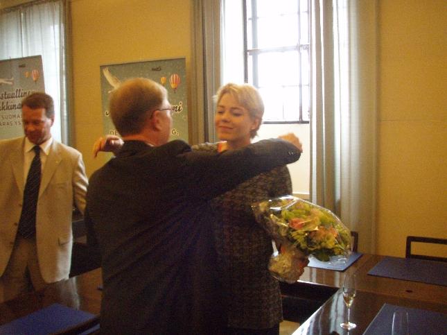 Ryhmäjohtajamme Pekka Ravi onnittelemassa kukkien kanssa Hennaa.