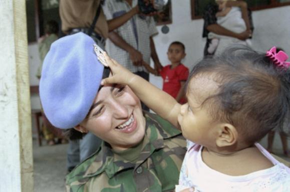 YK:n UNTAET-operaation rauhanturvaaja leikkii pienen Hera tytön kanssa Itä-Timorissa vuonna 2000. Kuva: UN Photo/Eskinder Debebe